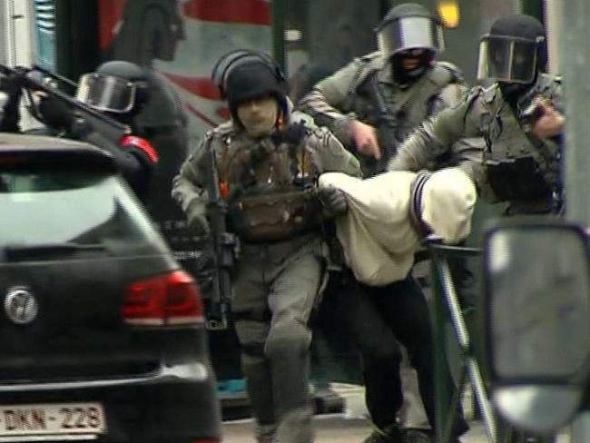 Armed police officers escort a suspect to a police vehicle during a raid in the Molenbeek neighbourhood of Brussels on Friday. Picture: VTM via AP