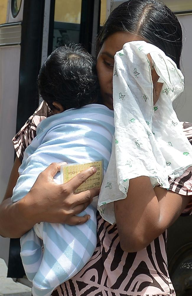 A Sri Lankan asylum seeker with a baby prepares to enter the magistrates' court in Galle after being returned by Australia.