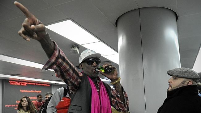 Former NBA basketball player Dennis Rodman gestures as he has a drink while checking in for his flight to North Korea at Beijing's international airport on January 6.