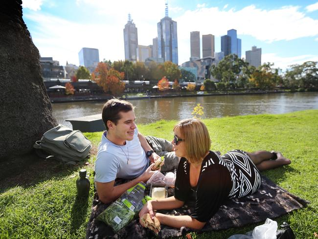 Andrew Wood-Collier and Emma Hall soak up the Melbourne sunshine with a picnic on the Yarra. Picture: Alex Coppel