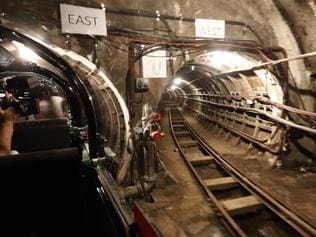A cameraman films the Mail Rail tunnels that belong to the Postal Museum in London, Wednesday, July 26, 2017. London's newest tourist attraction is perfect for underground explorers. It's not ideal for the claustrophobic. A visit to Mail Rail, a subterranean train network that once carried millions of letters a day across the city, involves a cramped journey through dark tunnels 70 feet (21 meters) below the surface, on a very small train. It's atmospheric, but not roomy. (AP Photo/Frank Augstein)