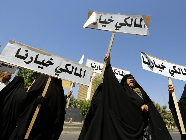 "Political crisis ... Iraq women carry placards which read in Arabic ""[Nuri] Al-Maliki is our choice"" during rally to show their support for outgoing prime minister Nuri al-Maliki. Picture: AFP"