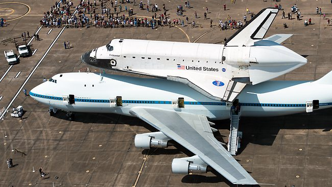 A crowd gathers around the space shuttle Endeavour, carried atop NASA's 747 Shuttle Carrier Aircraft, after landing at Ellington Field in Houston, on its way from the Kennedy Space Center to the California Science Center in Los Angeles, where it will be placed on permanent display. (AP Photo/Houston Chronicle, Smiley N. Pool, Pool)