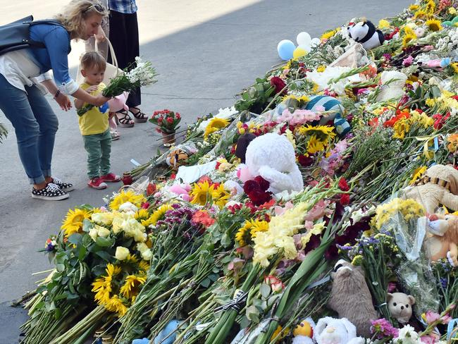 Seeking answers ... a woman and her son lay flowers at the Netherlands embassy in Kiev on July 21, 2014. Picture: Sergei Supinsky