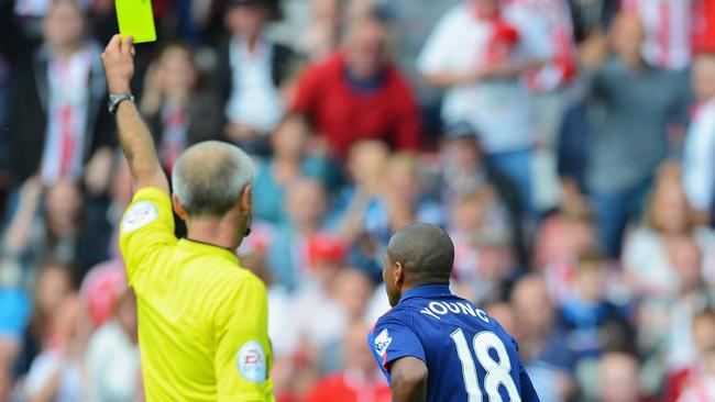 Referee Martin Atkinson shows the yellow card to Ashley Young for simulation.