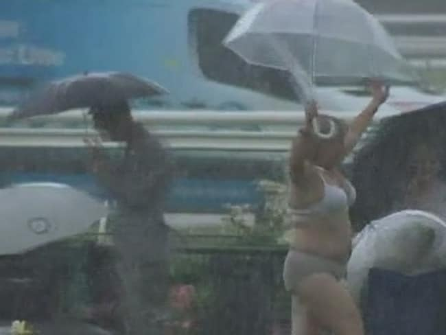 A woman strips down at the rainy Oaks Day.