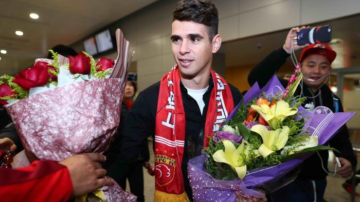Brazilian football player Oscar (C) receives flowers as he arrives at Shanghai airport on January 2, 2017. Brazilian midfielder Oscar landed in Shanghai on January 2, 2017 where the 25-year-old was set to smash the Asian transfer record with a reported 63 million USD deal with Shanghai SIPG. / AFP PHOTO / STR / China OUT