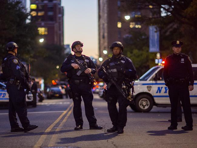 Heavily armed police stand guard near the scene after a motorist drove onto a busy bicycle path near the World Trade Center memorial and struck several people. Picture: AP