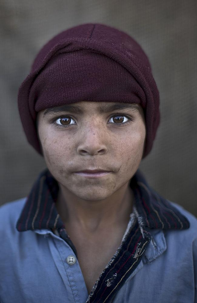 Afghan refugee boy, Noorkhan Zahir, 6, poses for a picture, while playing with other children in a slum on the outskirts of Islamabad, Pakistan.