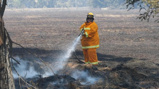 Fire fighters mop up hot spots south of Cobden as bushfires worsen. Picture: AAP/David Crosling