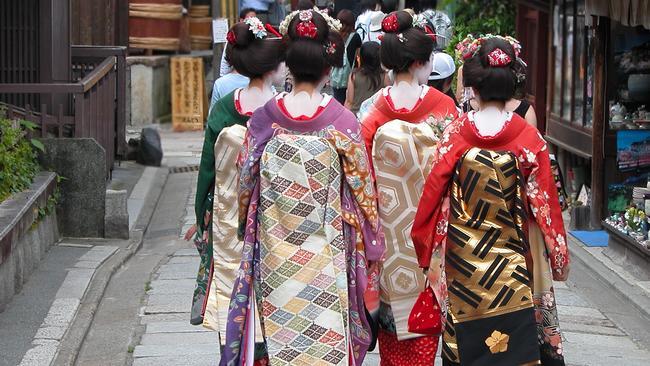 A group of geishas on a street in Kyoto.