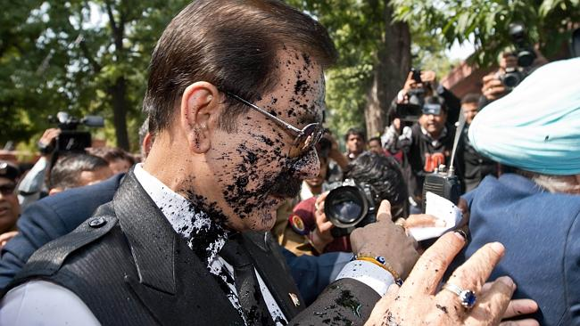 Covered in ink... India's Sahara group chairman Subrata Roy enters court after he was splashed with blank ink by an angry investor. Picture: AP