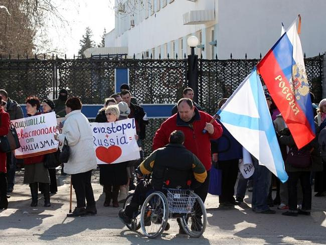 Choose your side ... pro-Moscow protesters gather in front of the Ukrainian Navy Base in Sevastopol while unidentified armed men block the gate with Ukrainian soldiers trapped inside. Picture: Ella Pellegrini