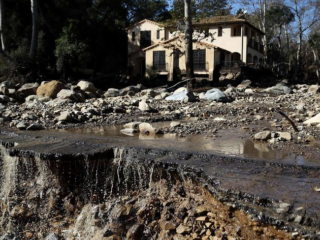 Water pours off of a road that was damaged by a mudslide. Hundreds are still stranded after massive mudslides crashed through Montecito, California early Tuesday morning. Picture: Justin Sullivan/Getty Images/AFP