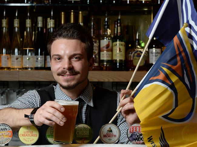 Big business: Subiaco Hotel barman Vedran Yaksich raises a glass to football. Picture: Daniel Wilkins