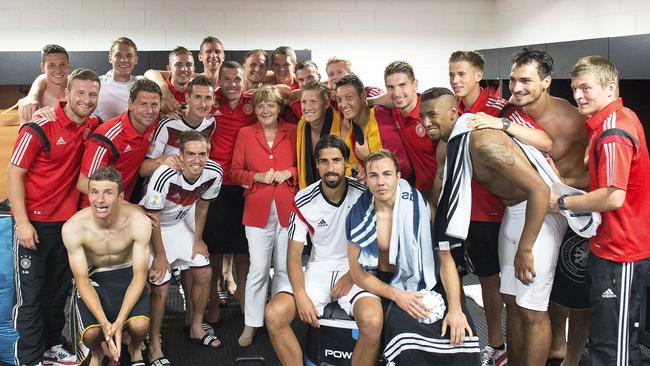 German Chancellor Angela Merkel (C) poses with the German squad.