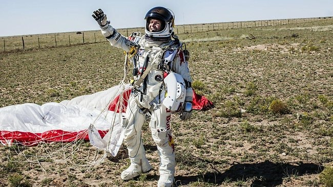 Felix Baumgartner waves to his ground crew after landing safely following his record-breaking freefall from the stratosphere. Picture: Red Bull