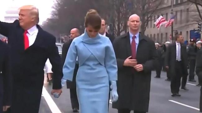 The agent appeared tense as he walked behind the new First Lady while thousands of supporters lined the streets