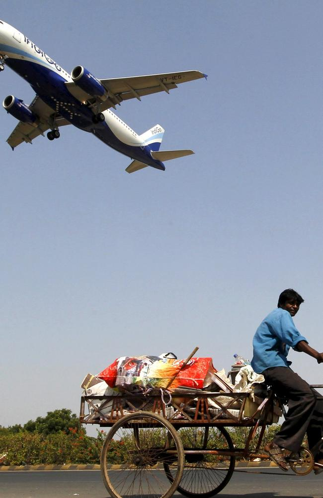 Airline confession ... An IndiGo Airlines aircraft prepares to land as a man pedals his cycle in Ahmedabad, India. (File)