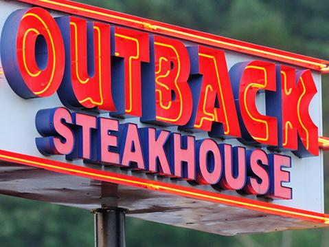 """""""Huntsville, Alabama, USA - June 9, 2011: Outback Steakhouse sign illuminated in the early evening. Sign located on Whitesburg Drive in Huntsville, Alabama."""""""