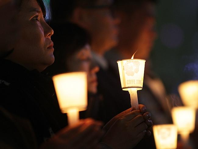 Candlelight vigil ... Students and citizens hold candles as they pray for the safe return of missing passengers who were travelling aboard South Korean ferry the Sewol.