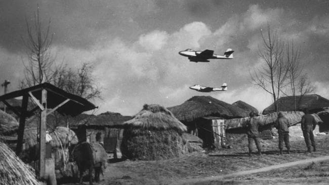 Meteor jets of the RAAF's No. 77 fighter squadron flying over village in Korea as they head for their targets while being watched by three RAAF ground crew during the Korean War in 1953.