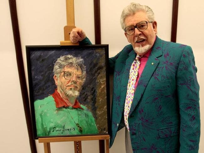 An artist ... Rolf Harris with his self portrait at the National Portrait Gallery in 2008, the portrait gallery has since removed the painting from view. Picture: Ray Strange
