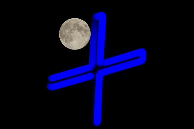 A full moon is seen behind the neon cross of a church in Skopje in Macedonia on August 31, 2012. Photo: AFP