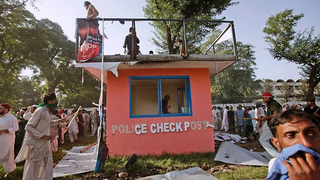 Pakistani protesters destroy a police guard shack during clashes that erupted as protestors tried to approach the U.S. embassy, in Islamabad. (AP Photo/Muhammed Muheisen)