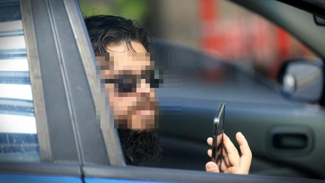 A driver who was booked for using his mobile phone while driving in Brisbane. Picture: Jamie Hanson.