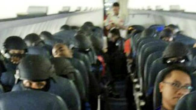 Grim plane ride ... Bali Nine ringleader Myuran Sukumaran, at left, appears to sleep on board the plane taking the pair to Cilacap airport.
