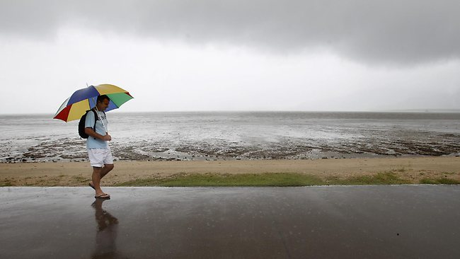 Andy Hodgson from England takes a wet walk on the Esplanade in Cairns. Picture: Stewart Mclean