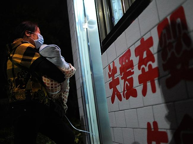 A woman holds her baby as she walks into a baby hatch. Picture: China Foto Press