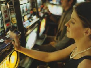 Woman gambling on slot machine in casino, side view