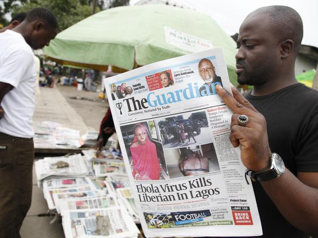 A man reads about the outbreak in Nigeria. Pic: AP/Sunday Alamba.
