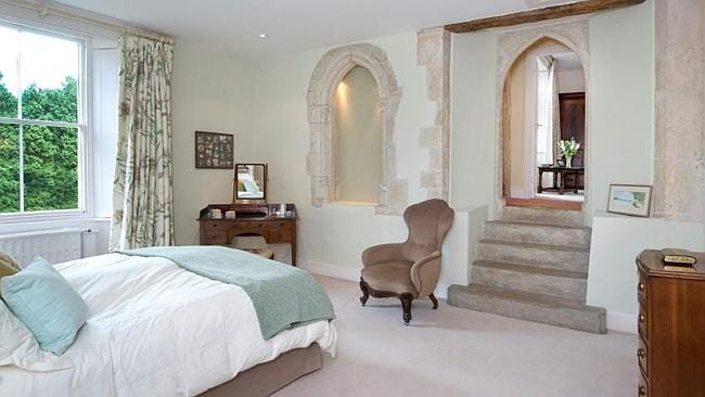 Down several steps is one of the property's five large bedrooms. Picture: Supplied.