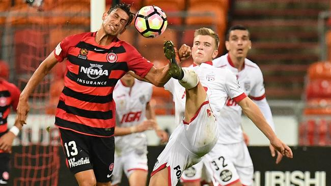 Adelaide United's Riley McGree (right) challenges the Wanderers' Bruno Pinatares for the ball on Saturday night.