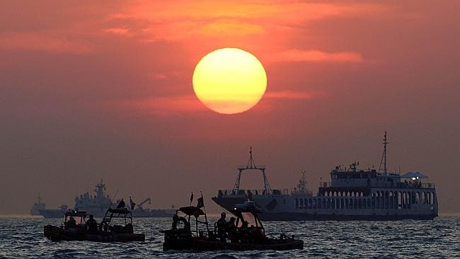 Search effort... Workers and divers silhouetted against the sunset in Jindo. Picture: Nicolas Asfouri