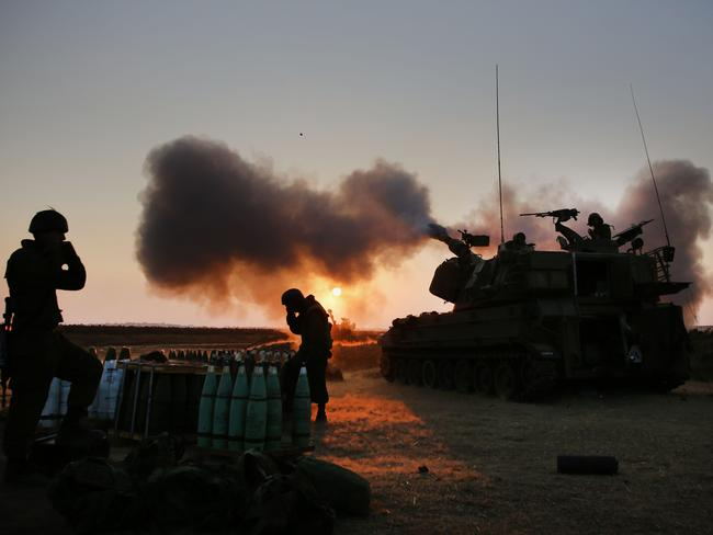 Fighting rages ... Israeli soldiers fire towards the Gaza Strip from their position near the border.