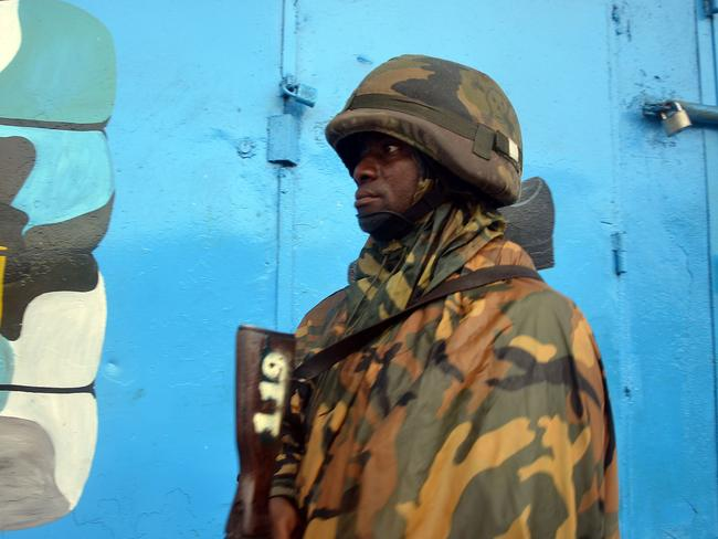 Shop shut ... A Liberian soldier stands guard outside a closed shop in Monrovia's West Point slum as part of quarantine measures to contain the spread of Ebola. Pic: AFP/ZOOM DOSSO