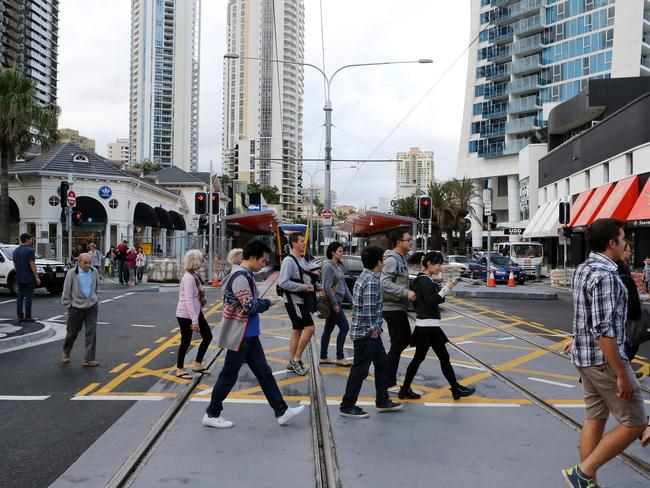 Pedestrians cross the tram tracks in Surfers Paradise. Picture by Scott Fletcher