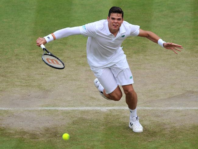 Milos Raonic plays a sliced backhand to Nick Kyrgios before charging to the net.