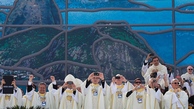 Cardinals, bishops and priests take photos as they wait for the arrival of Pope Francis and the start of the World Youth Day closing Mass in Rio de Janeiro, Sunday, July 28, 2013. Pope Francis concluded the first pastoral trip of his pontificate to Brazil where he attended the 2013 World Youth Day in Rio. (AP Photo/Domenico Stinellis)
