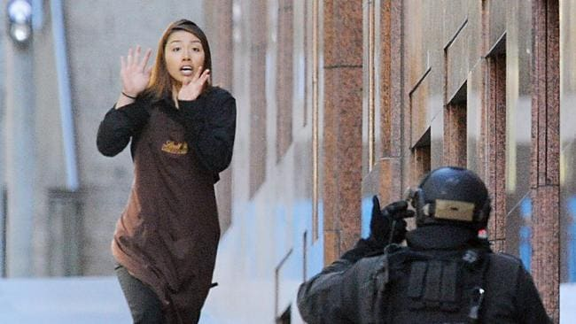 Elly Chen runs from the Lindt Cafe with her hands raised. Picture: AAP Image/Joel Carrett