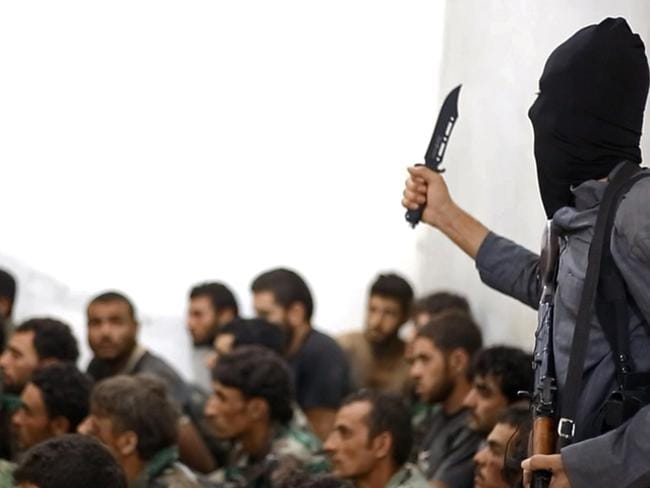 A fighter from the Islamic State group, armed with a knife and an automatic weapon, next to captured Syrian army soldiers and officers, following the battle for the Tabqa air base, in Raqqa, Syria. Picture: AP