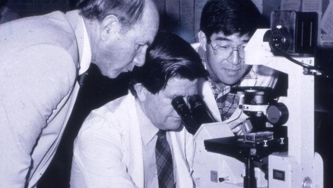 Professor George Yeoh (right) with the microscope he bought with his first Cancer Council WA grant.