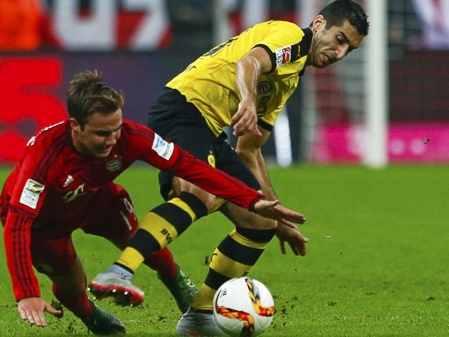 Bayern Munich's Mario Goetze (L) fights for the ball with Borussia Dortmund's Henrikh Mkhitaryan.