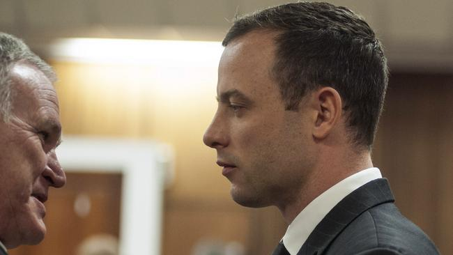 Defence ... Oscar Pistorius talks to his lawyer Barry Roux in the dock.
