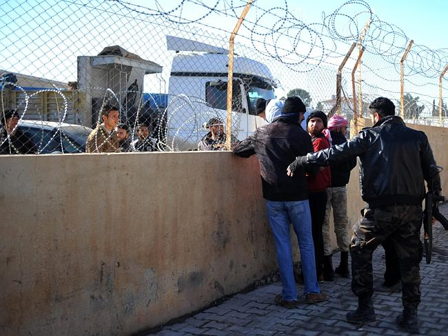 A Turkish policeman warns Syrian refugees crossing illegally the southern border gate of Akcakale on January 11, 2014 in Sanliurfa.