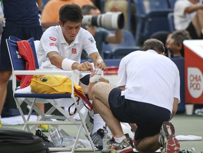 Kei Nishikori applies tape to his toes during a medical time-out between games against Stan Wawrinka.